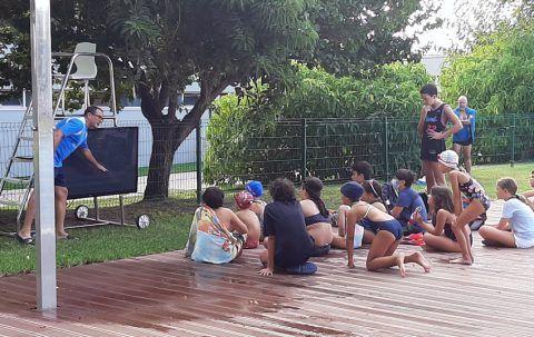 Los niños aprenden de los nadadores olímpicos